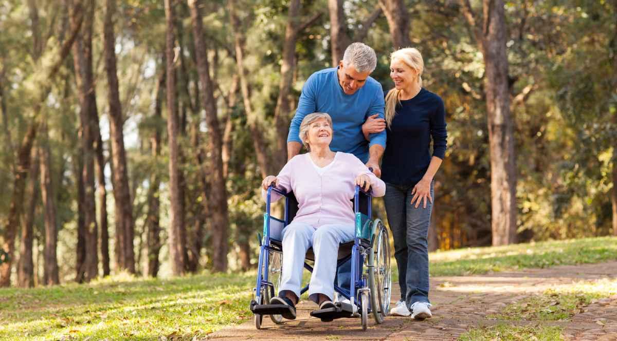 gezin met rolstoel wandelend in bos