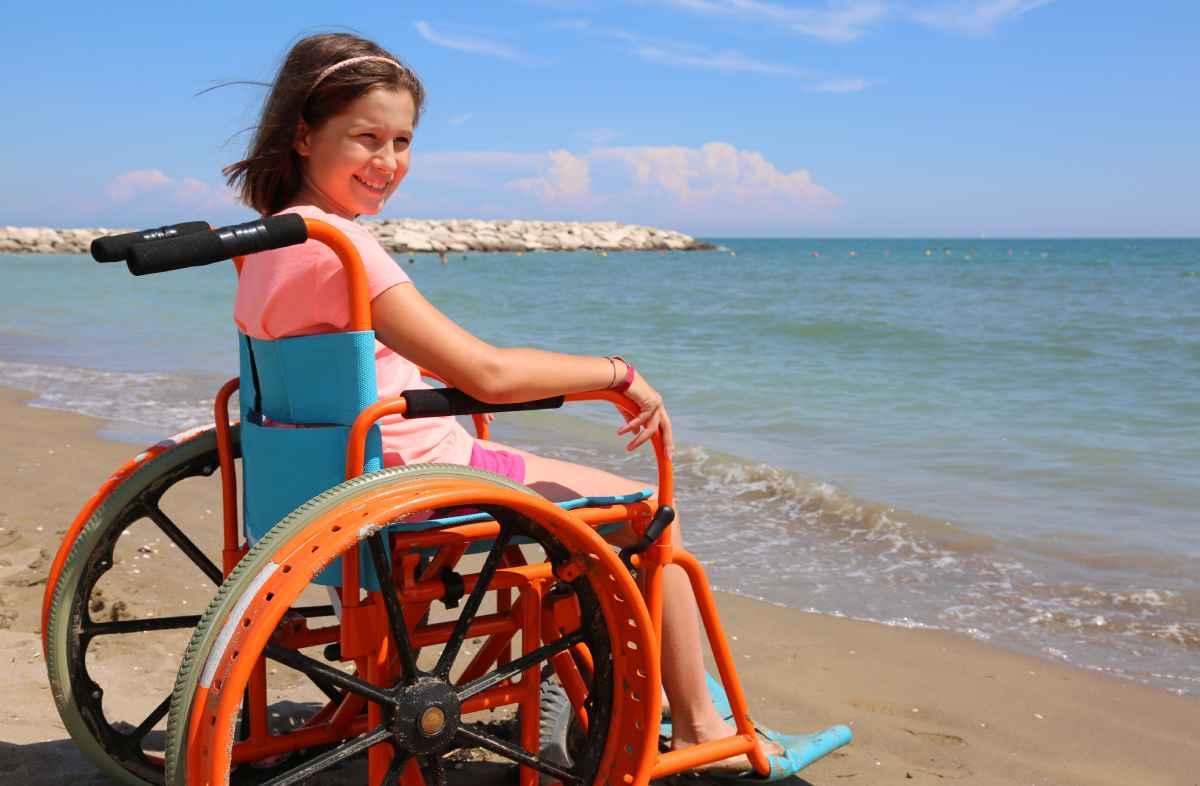 kind in strandrolstoel aan zee